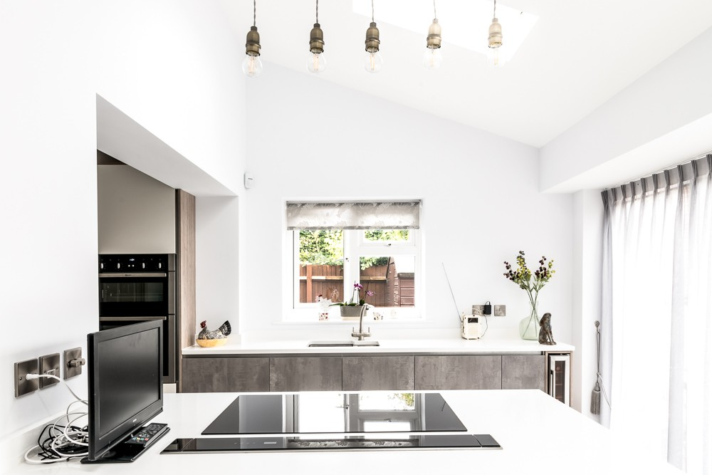White kitchen with electric hob that rises from the work surface