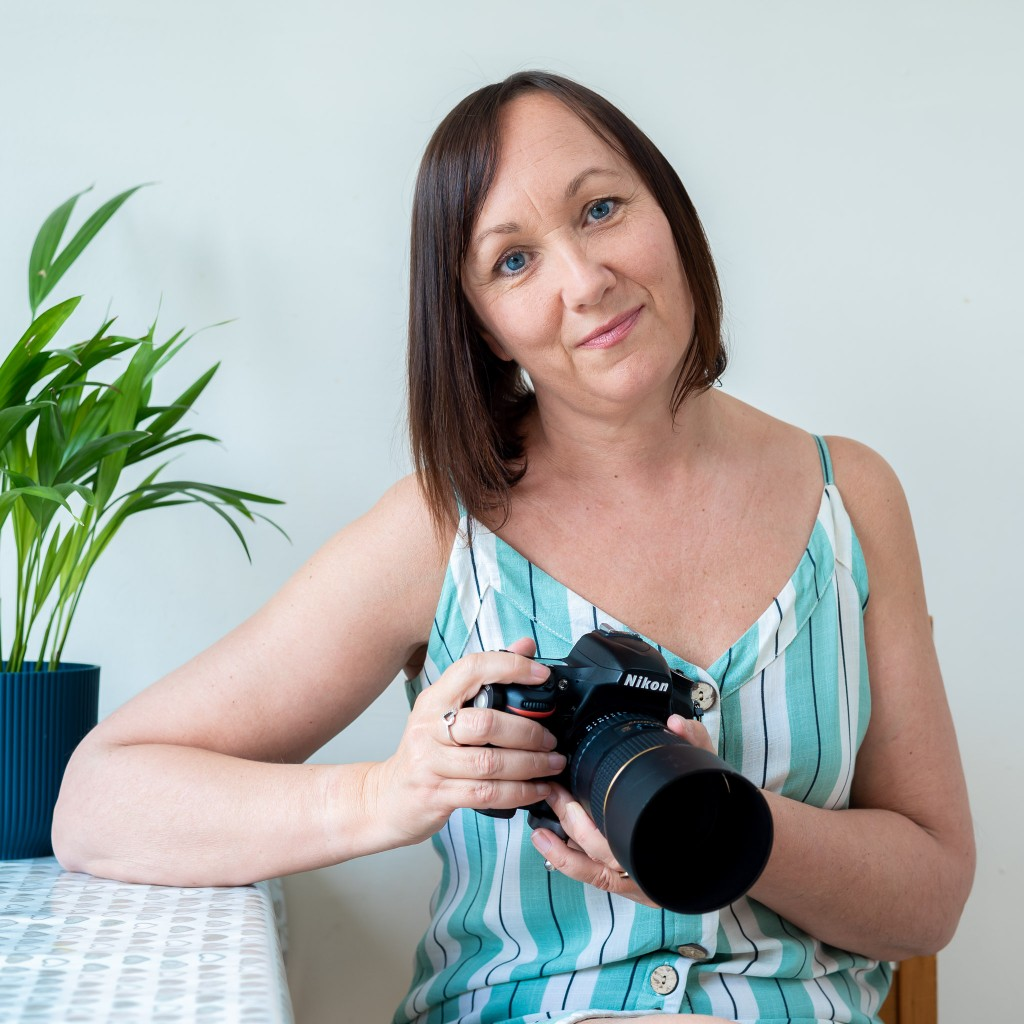 Brand photographer image with teal and white striped dress and Nikon camera
